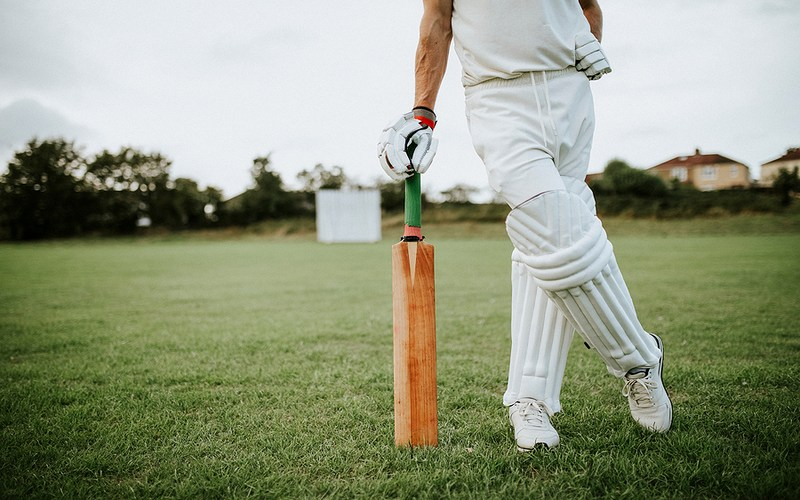 Cricket Player Leaning on Bat